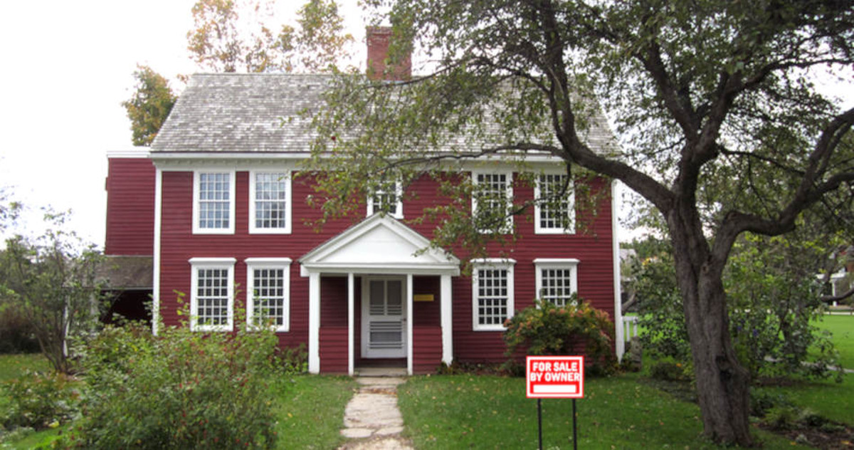 two story brick red house with for sale sign