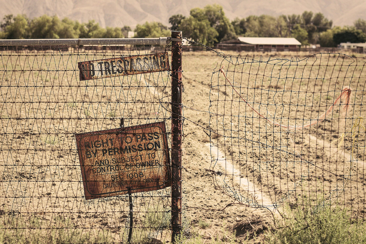 Country property with dirt road access blocked with fence and sign saying no trespassing on it.
