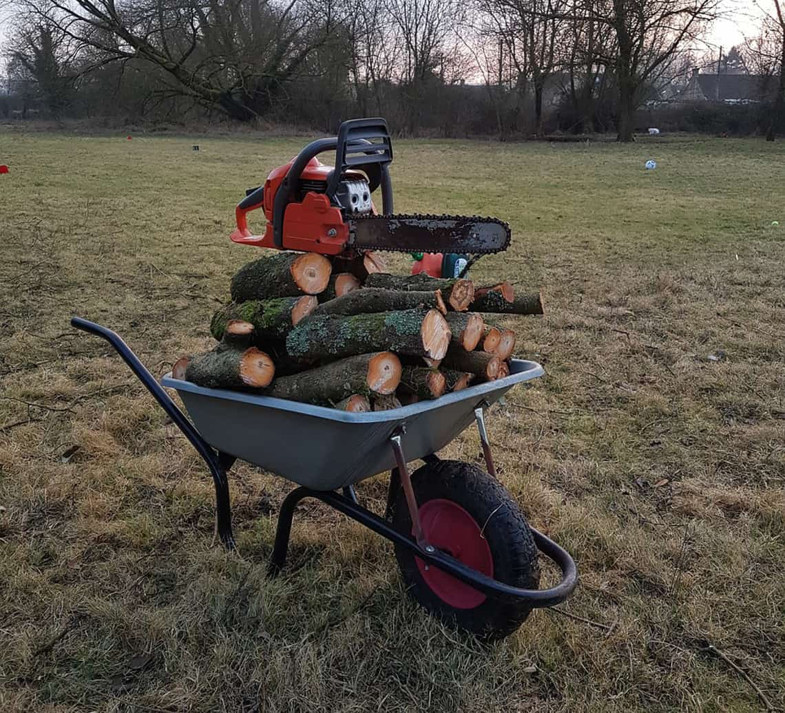 wheelbarrow full of cut wood topped with a chainsaw