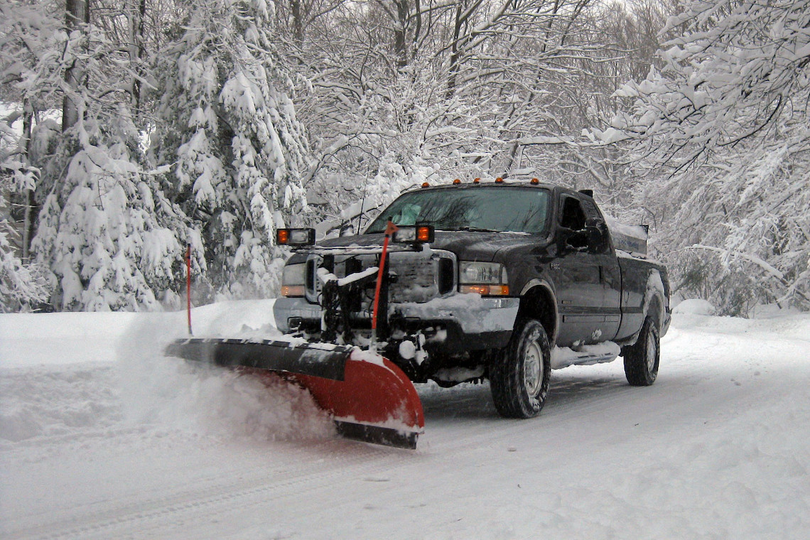 Black Ford F-150 pickup truck with red snow plow blade on the front of the truck plowing snow in the country. flickr.com-photos-joeloong-4337103340-in-photoist.jpg-IMG_2523-CC-BY-SA-2.0-.jpg