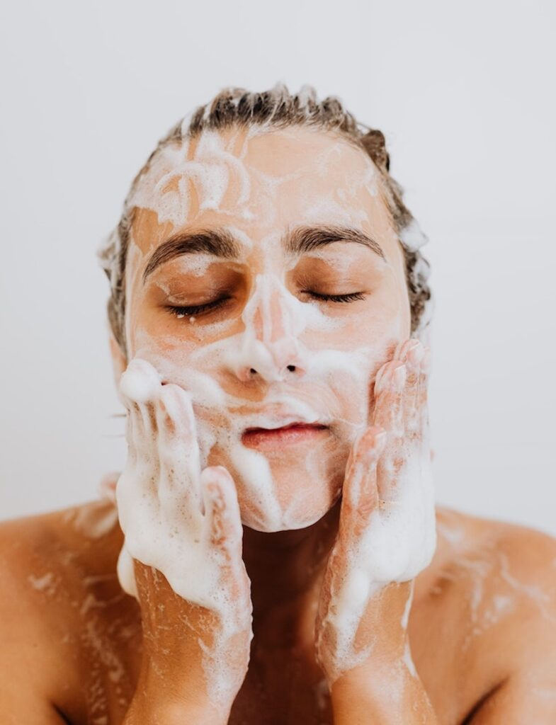 woman washing face with soap